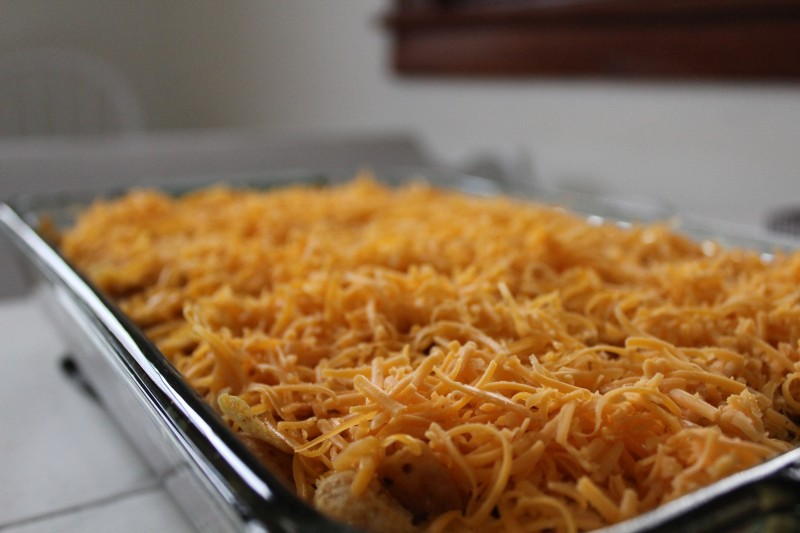chicken taco bake topped with cheese and ready for the oven