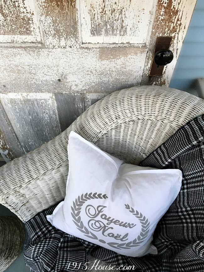 Chippy salvage door paired with a wicker chair, a blanket scarf and a DIY pillow and you've got a great Christmas decor idea! Click for details-