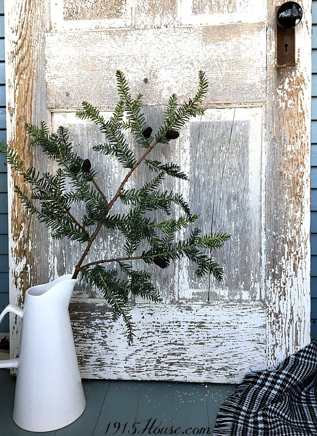 A salvage door, a pitcher and an evergreen branch - you've got a great accent piece for your holiday home!