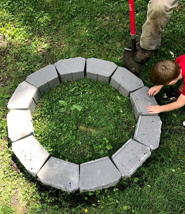 Laying out fire pit blocks before cutting into the soil.