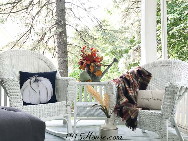Fall front porch decor is made complete with layers of comfy throws and pillows to provide texture and warmth on those chilly Fall nights.